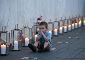 "Blake Catanese sits near 40 candles at the Flight 93 Memorial Wall for ...""widows and orphans""."